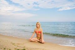 Het praktizeren van de yoga bij het strand Stock Foto's