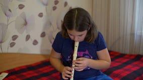 Het praktizeren van het meisje fluit thuis stock video