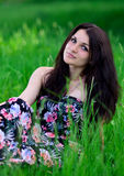 Het prettige, goede, leuke, vriendschappelijke meisje met interessante blik, zicht, mooie kleding zit op zeer heldergroen gras in Royalty-vrije Stock Fotografie