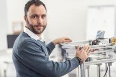 Het prettige jonge ingenieur stellen met 3D printer in bureau Royalty-vrije Stock Foto's