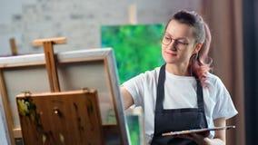 Het prettige jonge onbezorgde vrouwelijke beeld van de schilderstekening bij werkruimte middelgroot close-up stock video