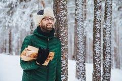 Het prettige kijken gelukkig mannetje houdt brandhout, kijkt zorgvuldig opzij, bevindt zich dichtbij de winterbomen, droomt over  stock afbeelding