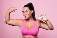 Het prettige mollige vrouw stellen op roze achtergrond Stock Afbeelding