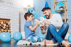 Het prettige zoon en vader vechten met stuk speelgoed robots Royalty-vrije Stock Foto's