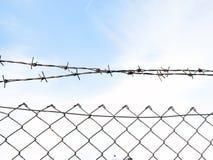 Het prikkeldraad in twee rijen als bescherming tegen onbevoegde ingang in privé grondgebied stock fotografie