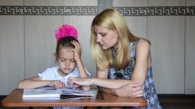 Het privé-leraarmeisje verklaart de betekenis van de taak in handboek stock video