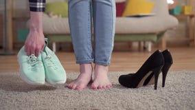 Het probleem om een vrouw te kiezen kiest tennisschoenen in plaats van schoenen met hielen stock video