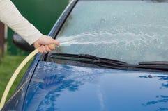 Het proces om auto's met een slang met water te wassen Royalty-vrije Stock Fotografie