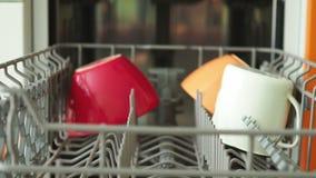 Het proces om de afwasmachine schone schotels leeg te maken stock videobeelden