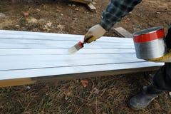 Het proces om de panelen van het pijnboomhout met een borstel en een witte verf te schilderen royalty-vrije stock foto's