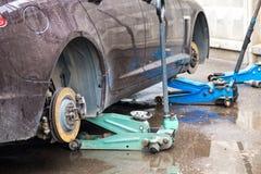 Het proces om de zomerbanden met de winterbanden te vervangen De auto is bij het nivelleren van hefbomen op het asfalt royalty-vrije stock afbeeldingen