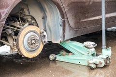Het proces om de zomerbanden met de winterbanden te vervangen De auto is bij het nivelleren van hefbomen op het asfalt stock afbeeldingen