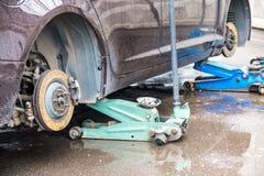 Het proces om de zomerbanden met de winterbanden te vervangen De auto is bij het nivelleren van hefbomen op het asfalt stock foto