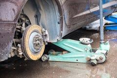 Het proces om de zomerbanden met de winterbanden te vervangen De auto is bij het nivelleren van hefbomen op het asfalt stock fotografie