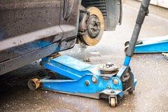 Het proces om de zomerbanden met de winterbanden te vervangen De auto is bij het nivelleren van hefbomen op het asfalt royalty-vrije stock afbeelding