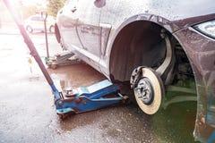 Het proces om de zomerbanden met de winterbanden te vervangen De auto is bij het nivelleren van hefbomen op het asfalt stock afbeelding
