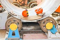 Het proces om een cilindrisch lichaam voor een container, een warmtewisselaar op broodjes, door het rollen, het lassen en oranje  stock foto's