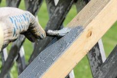 Het proces om een houten deklaag met een borstel met grijze verf te schilderen royalty-vrije stock afbeeldingen