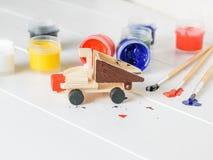 Het proces om een houten vrachtwagenstuk speelgoed op een witte lijst te verfraaien Stock Afbeeldingen