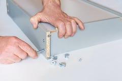 Het proces om een keukendoos door de handen van een bejaarde te assembleren Het sleutelvakmuren van de bandhexuitdraai stock foto