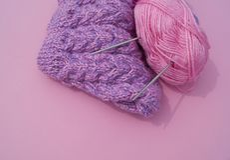 Het proces om een lilac GLB te breien Garens op een roze achtergrond Comfortabel garen stock afbeelding