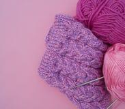 Het proces om een lilac GLB te breien Garens op een roze achtergrond Comfortabel garen royalty-vrije stock fotografie