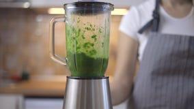 Het proces om groene smoothie in een keukenmixer voor te bereiden stock videobeelden
