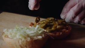 Het proces om grote Hamburger te koken is een professionele chef-kok, close-up Zet pasteitjes met kaas op een broodje stock video