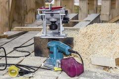 Het proces om hout te behandelen, Timmerman die met molen werken stock foto