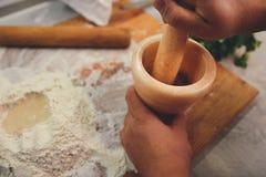 Het proces om kruiden in een steenmortier te malen stock foto's