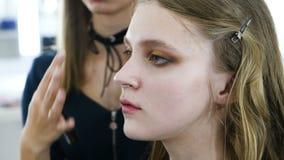 Het proces om make-up op het gezichtsmodel toe te passen Poeder, oogschaduw, borstel voor het toepassen van make-up Het hoofdgezi stock videobeelden