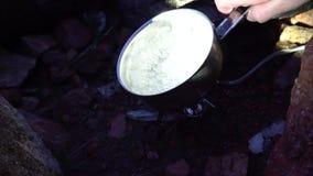 Het proces om op de brander te koken Draagbaar fornuis onder de stenen De brand brandt stock videobeelden
