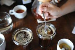 Het proces om tot een kom te vormen Het proeven vers brouwde koffie met lepels Koffietoebehoren op de lijst stock foto