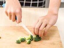 Het proces van chef-kok het koken - het snijden bloemkolen op scherpe raad Stock Foto