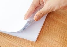 Het proces van het pagineren wit bureaudocument met uw vingers Stock Foto