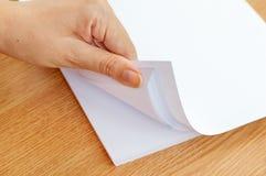 Het proces van het pagineren wit bureaudocument met uw vingers Stock Fotografie