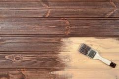 Het proces van het schilderen houten oppervlakten met een borstel Onvolledig p royalty-vrije stock afbeelding