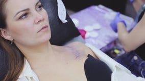 Het proces van tatoegerings hoofdmeisje maakt een druk op de borst stock footage