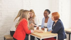 Het proces van het teamwerk Multiraciale groep vrouwen die in open plekbureau coloborating stock video