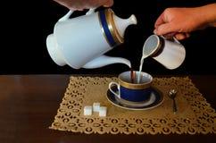 Het proces van het uitgieten van koffie met melk stock afbeelding