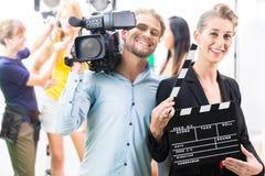 Het productieteam met camera en neemt klap op filmreeks of studio stock afbeeldingen