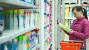 Het Productinformatie van de vrouwenlezing terwijl het Winkelen stock footage