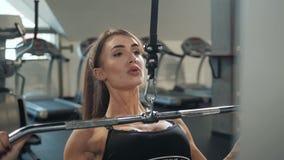 Het professionele atletische meisje van de trainersport met perfect fitness lichaam die training harde opleiding met bar op helli stock video