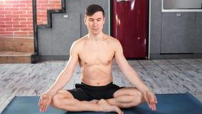 Het professionele atletische yogimens praktizeren die mediterend binnen volledig schot ademen stock video