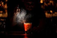 Het professionele barman bespuiten aan het cocktailglas met één groot ijsblokje in dark stock foto
