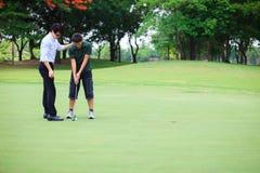 Het professionele golfspeleronderwijs om golf te spelen Stock Foto's