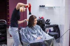 Het professionele haar van de kapper drogende cliënt stock afbeeldingen