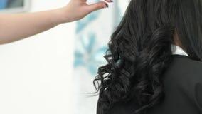 Het professionele kapsel, stilist maakt luxueuze krullen van lang haar van cliënt in schoonheidssalon stock footage