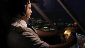 Het professionele navigerende vliegtuig van de vliegtuigbemanningsbevelhebber boven stad bij nacht stock videobeelden