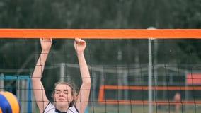 Het professionele volleyball dient vrouw op de strandtoernooien Netto het volleyball de speler blokkeert de mening wanneer het in stock video